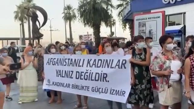 İzmir'de Taliban'ı protesto için toplanan bir grup kadın giydikleri temsili bir çarşafı çıkarıp yerlere attı